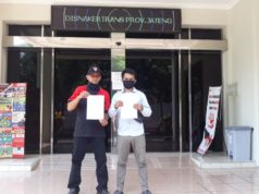 keterangan foto: Zainuri, dari Federasi Serikat Pekerja Indonesia Perjuangan (FSPIP) dan Herdin (Berbaju putih) membawa surat protes di depan kantor DISNAKERTRANS Provinsi Jawa Tengah [Doc. Alvin, LBH Semarang]