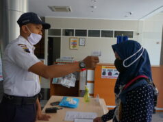 foto satpam yang melakukan pengecekan suhu kepada pengunjung