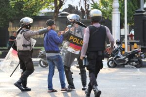polisi mencengkram kerah jaket demonstran [BP2M/Lalu]